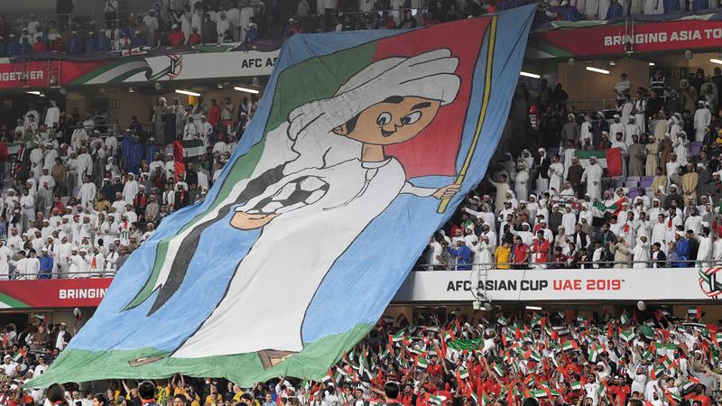 شعار كبير يحمل صورة تميمة البطولة (منصور) خلال مباراة الأبيض وأستراليا.  تصوير: أسامة أبوغانم