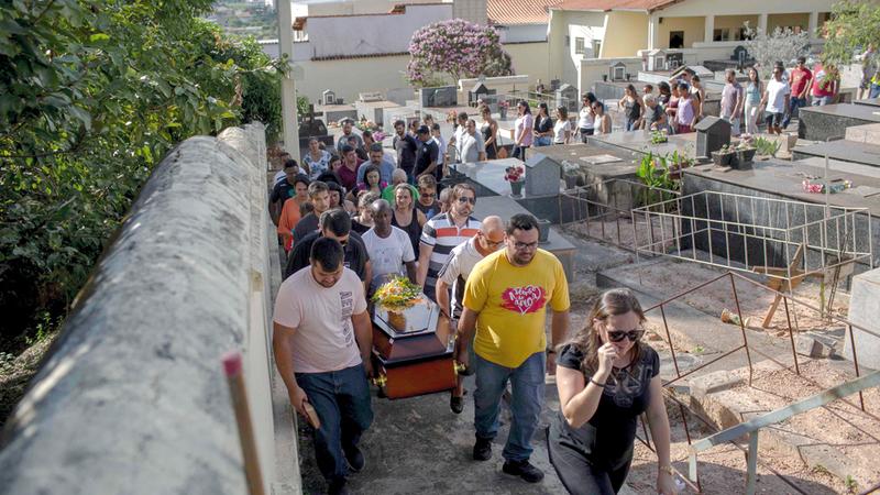 ذوو الضحايا يحملون جثامينهم إلى المقبرة.  أ.ف.ب