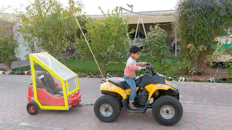 الأب صنع لـ «خالد» عربة آمنة مرتبطة بدراجة أخيه عمر.  تصوير: أحمد عرديتي