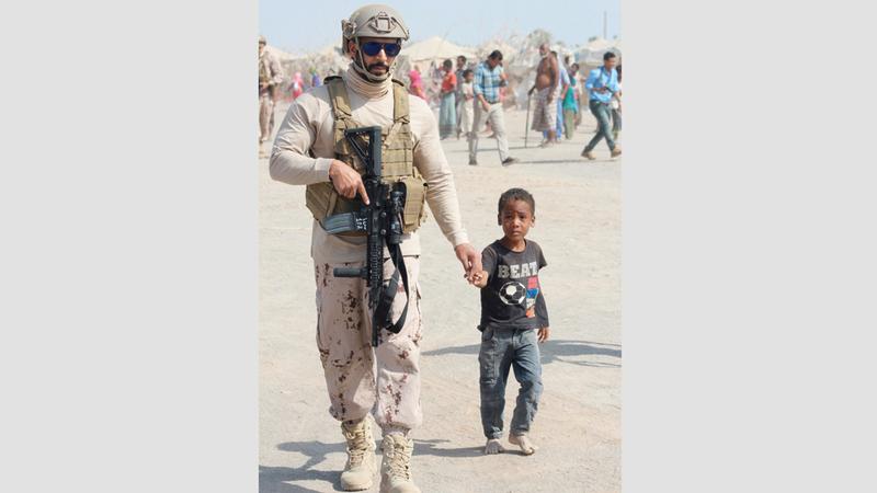 جندي من قوات التحالف يرافق طفلاً يمنياً نازحاً داخل أحد المخيمات في الحديدة. أ.ف.ب