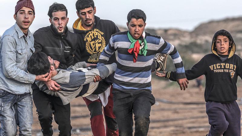فلسطينيون يحملون مصاباً في المواجهات مع الاحتلال شمال غزة.  إي.بي.إيه