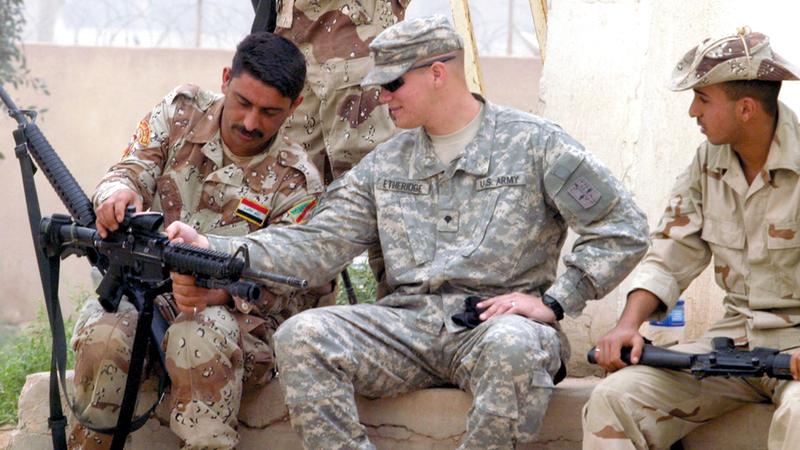 جندي أميركي يدرّب أحد الجنود العراقيين على كيفية استخدام السلاح. إي.بي.إيه