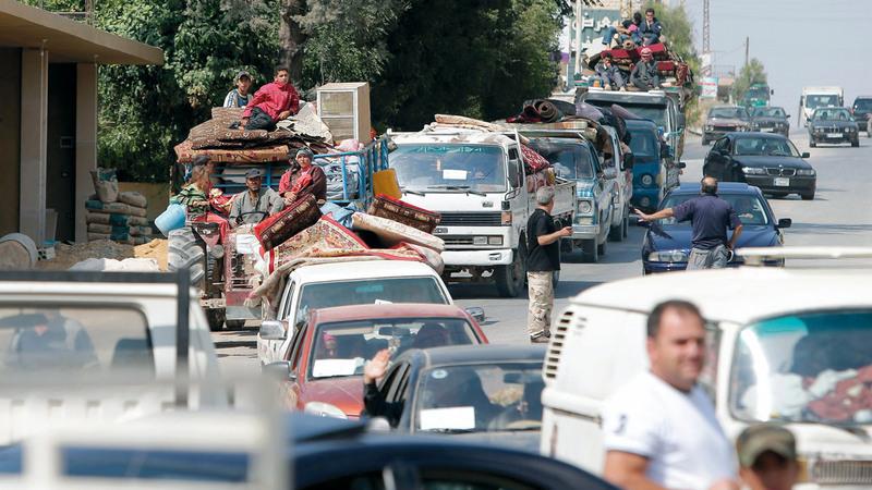سوريون عائدون إلى وطنهم من لبنان.  أ.ف.ب