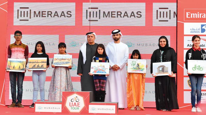 منصور بن محمد يتوسط الفائزين في مسابقة الرسم بحضور مطر الطاير. وام