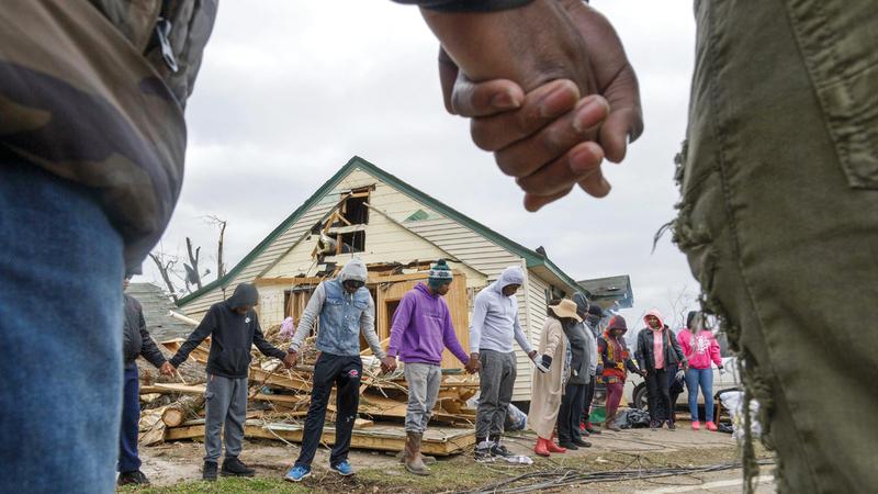 سلسلة بشرية للتضامن مع سكان منزل دمرته الأعاصير.  أ.ب