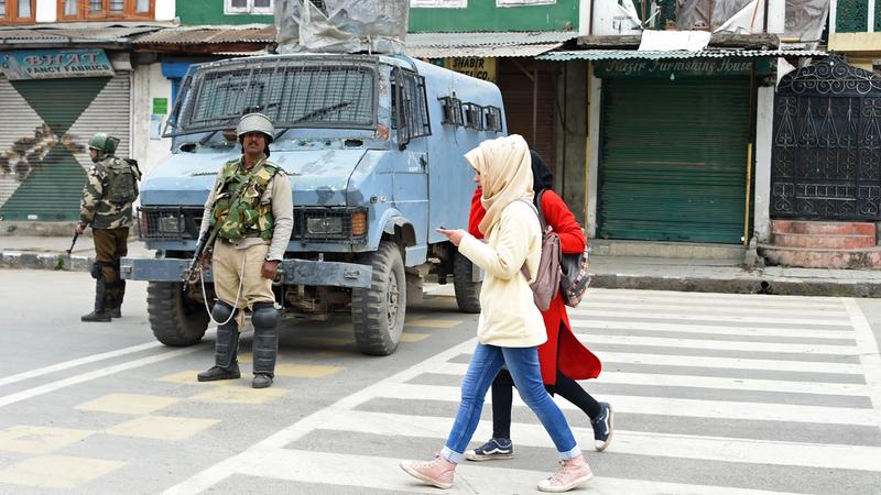 فتاتان كشميريتان تسيران من أمام قوات هندية في سريناجار. أ.ف.ب
