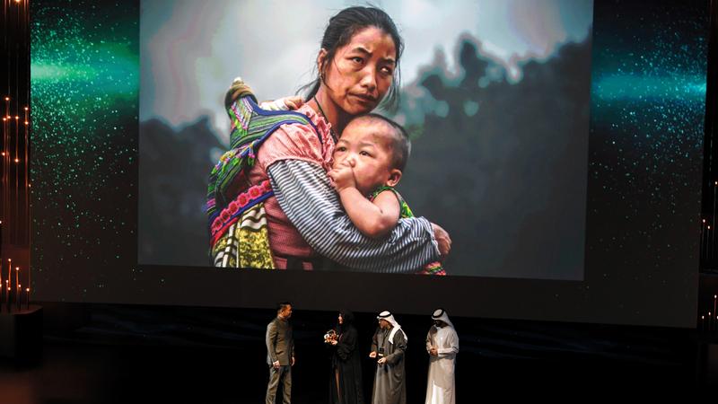 لطيفة بنت محمد تكرّم صاحب الصورة الفائزة بـ «الجائزة الكبرى».  تصوير: أشوك فيرما