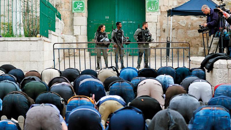 مقدسيون يصلّون خارج المسجد الأقصى بعدما أغلقته قوات الاحتلال. أ.ف.ب