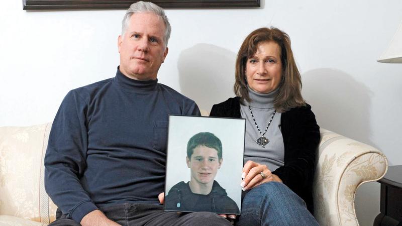 زوجان أميركيان يحملان صورة لولدهما المدمن  على الهيروين.  أرشيفية