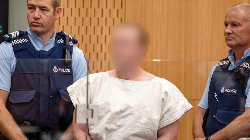 القاتل بين اثنين من أفراد الشرطة.  أ.ف.ب