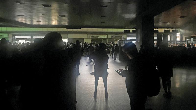المسافرون يقفون وسط الظلام في صالة المغادرين بمطار سيمون بوليفار بالعاصمة كراكاس.  رويترز