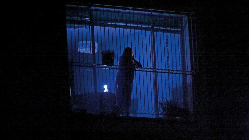 مواطن فنزويلي يلقي نظرة على الشوارع المظلمة  عبر نافذة بيته في كراكاس.  أ.ف.ب