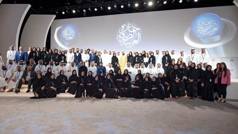 محمد بن راشد في لقطة تذكارية مع فريق نادي دبي للصحافة. من المصدر