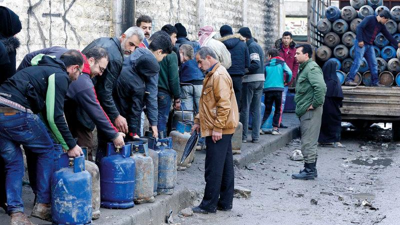 الناس في مدينة حلب يصطفون في طوابير من أجل الحصول على أسطوانات الغاز الشحيحة.  غيتي