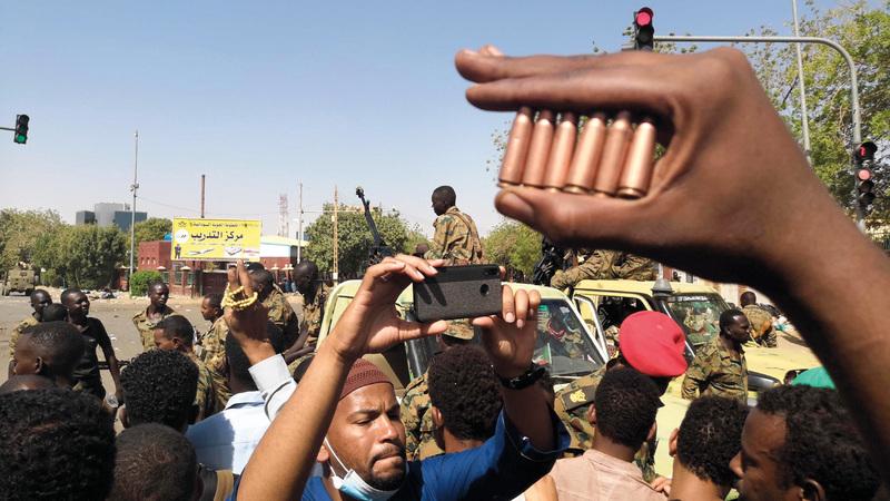 متظاهر يرفع رصاصات فارغة بعد تعرض المعتصمين بالخرطوم لهجوم الفجر. أ.ف.ب