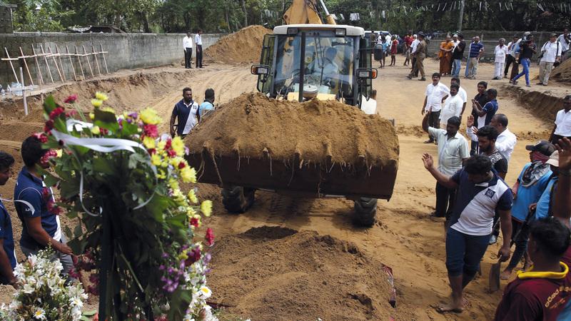 الأعداد الكبيرة للضحايا استدعت استخدام معدات ثقيلة أثناء الدفن. رويترز