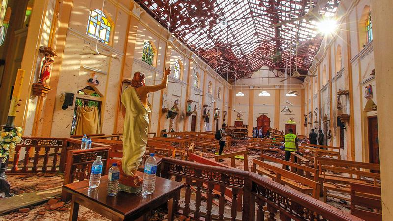 مسؤولون يتفقدون أحد مواقع التفجيرات داخل كنيسة. أسوشيتد برس