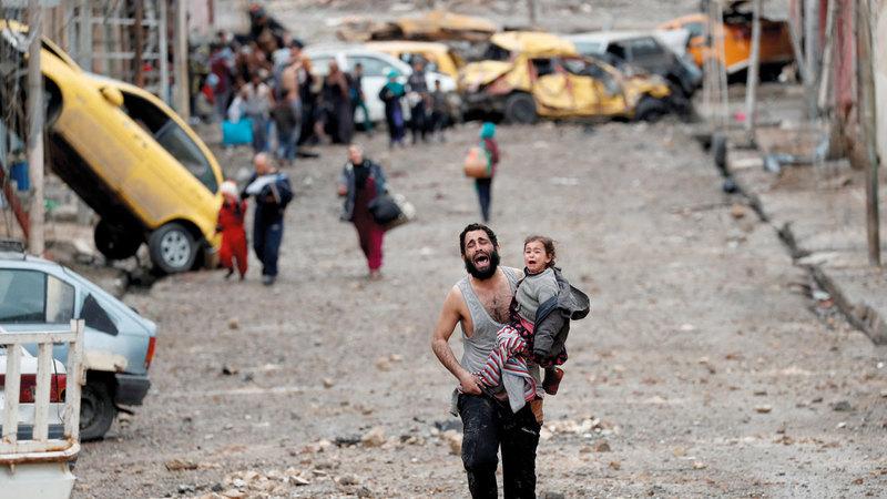 رجل يبكي وهو يحمل ابنته هرباً من جحيم «داعش» في الموصل. أرشيفية