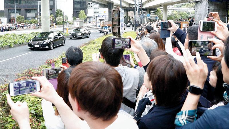 يابانيون يحاولون التقاط الصور للإمبراطور الجديد.  أ.ب