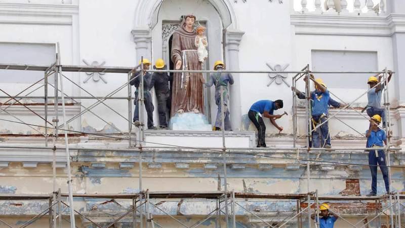 العمال يصلحون الدمار الذي لحق بكنيسة سانت أنطوني في الهجوم الانتحاري.  إي.بي.إيه