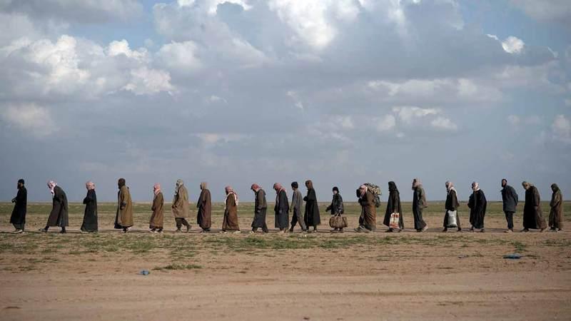 مجموعة من الرجال يسيرون نحو منطقة تفتيش بعد إخلائهم قرية بالقرب من باغوز آخر معاقل «داعش».  أ.ب