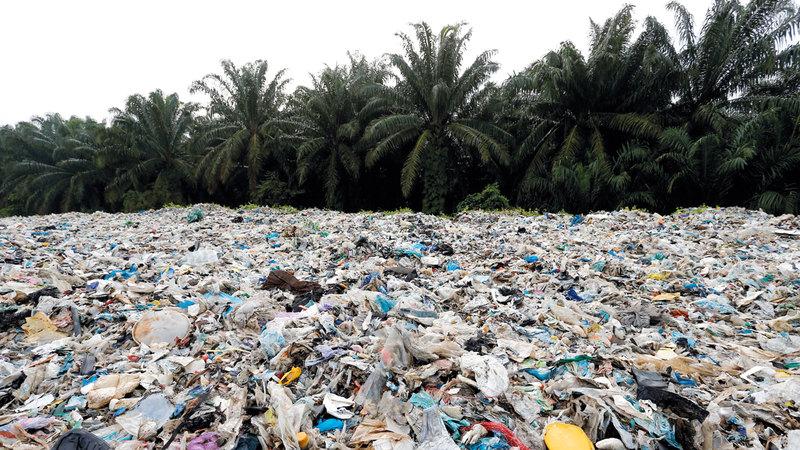 نفايات بلاستيكية مكدسة ملقاة خارج مصنع غير قانوني لإعادة التدوير بكوالا لانغات في ماليزيا.  رويترز