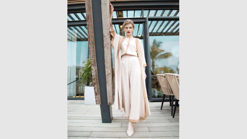 تتحول الخامات بين أنامل مصممة الأزياء الإماراتية أمل مراد إلى قطع تتسم بالبساطة الفاخرة.  من المصدر