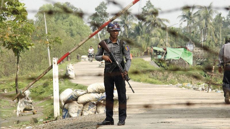 أحد ضباط شرطة ميانمار يقف في حراسة نقطة تفتيش شمال راخين.  أ.ب