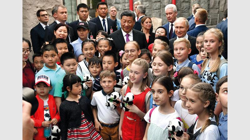 الزعيمان مع مجموعة من الأطفال يحملون مجسمات للباندا.  رويترز