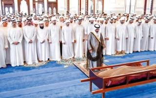 الصورة: حاكم أم القيوين وولي عهد دبي والشيوخ يؤدون صلاة الجنازة على جثمان منصور بن أحمد آل ثاني