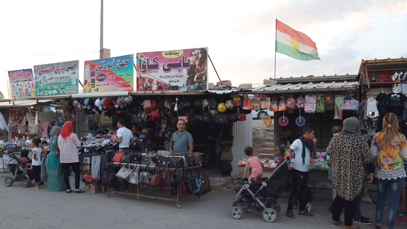 باعة جائلون يعرضون منتجاتهم خارج مخيم للاجئين في دهوك شمال العراق.  أ.ف.ب
