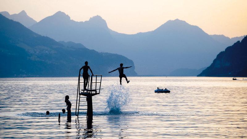فرنسيون يسبحون في بحيرة ريمس للتخفيف من آثار الحر.  إي.بي.إيه