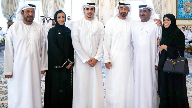 محمد بن زايد خلال استقباله الطالب أحمد الحوسني وأسرته. وام
