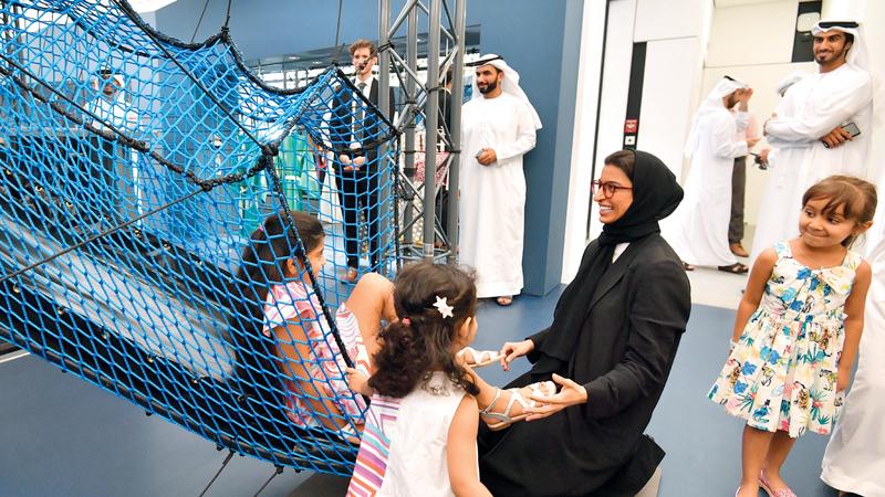 الوزيرة الكعبي تشارك الأطفال ألعابهم خلال افتتاحها المعرض. تصوير: نجيب محمد