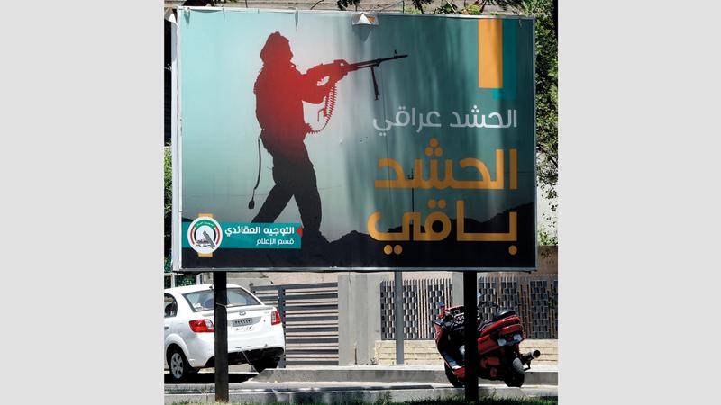 لوحة إعلانية تشير إلى أن الحشد الشعبي سيظل رغم مرسوم رئيس الوزراء. أ.ب