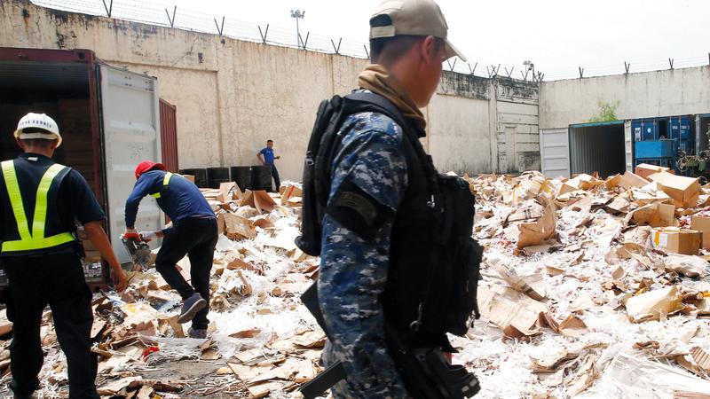 جندي يراقب موقع سجائر مقلدة تم تدميرها كجزء من محاربة الفساد. أ.ب