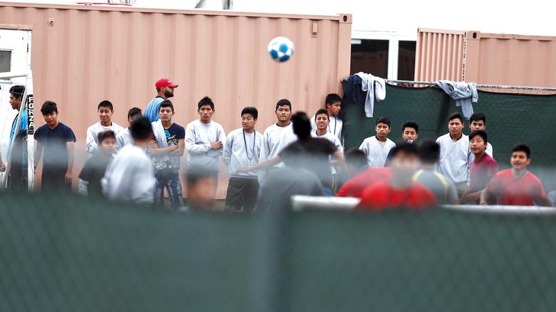 الأطفال المفصولون عن آبائهم يلعبون كرة القدم داخل مركز إيواء  لمحو الآثار النفسية المترتبة بإبعادهم.  أ.ب