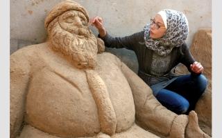 الصورة: فنانة غزية تنحت قضايا شعبها على الرمال