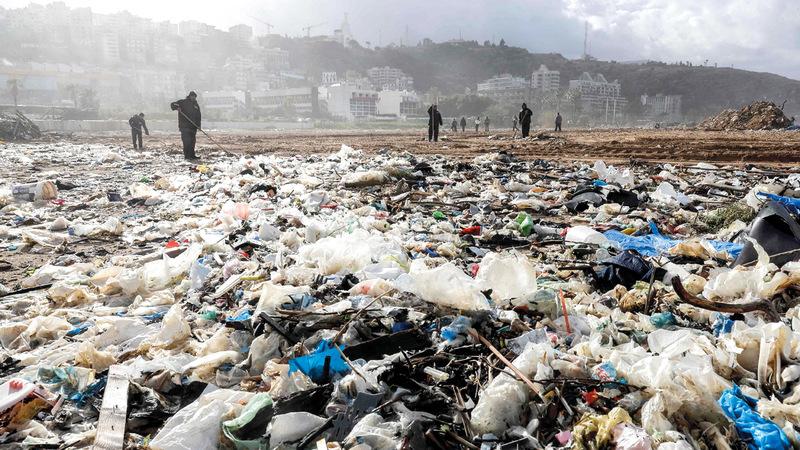 عمال ينظفون نفايات اختلطت بمياه الشاطئ.  أ.ف.ب
