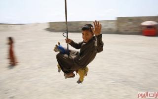 الصورة: بالصور.. فرحة العيد تحلّق على أرجوحة