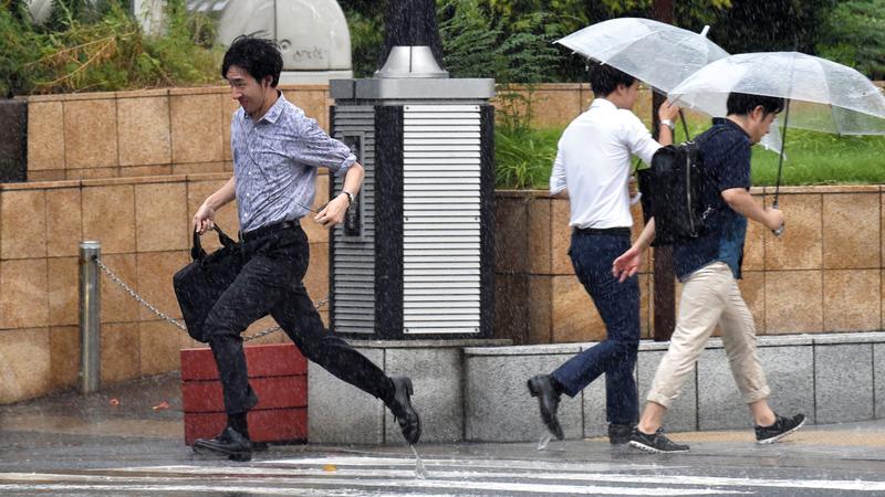 يابانيون يحتمون بالمظلات جراء الأمطار الغزيرة بسبب إعصار «كروسا». أ.ف.ب