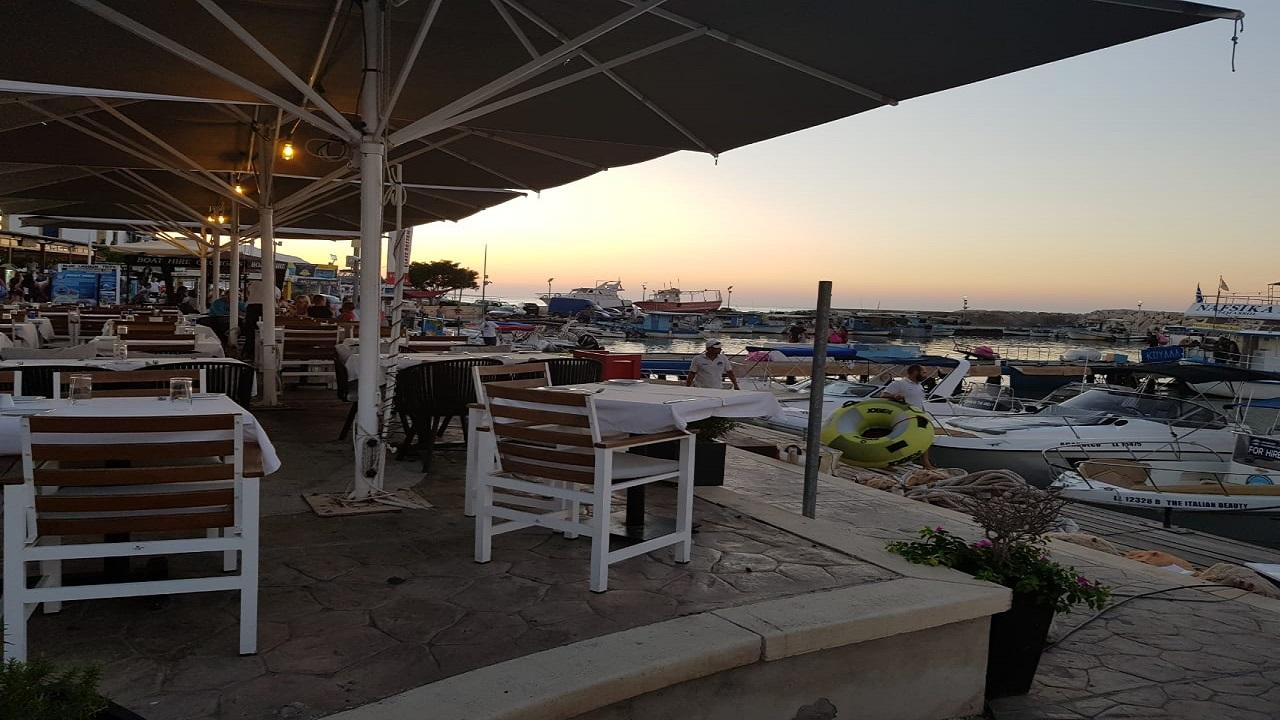 الاستمتاع بوجبة من الأسماك وثمار البحر الشهية التي تشتهر فيها جزيرة قبرص والتي تقدمها المطاعم الواقعة على ضفاف الميناء في مدينة بافوس