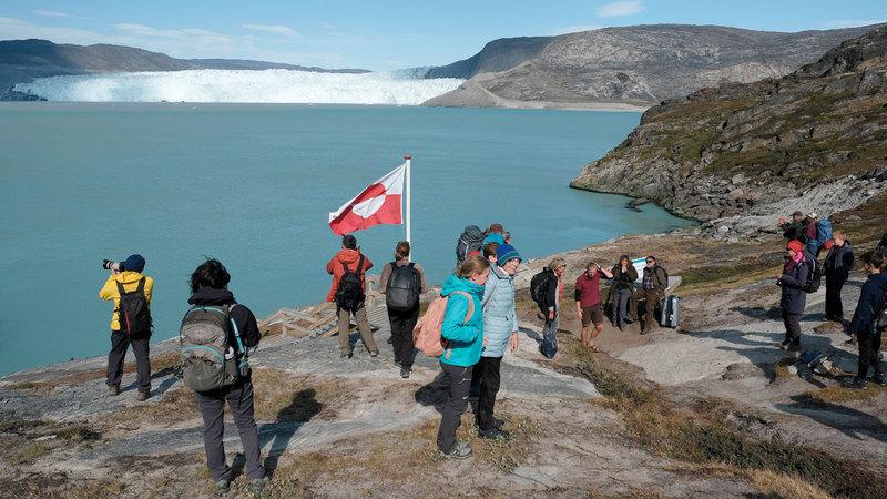 سياح في منطقة أكب سيرميا في غرينلاند يشاهدون نهراً جليدياً.  غيتي