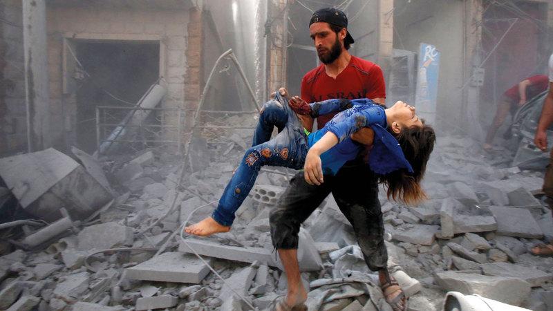 رجل يقوم بإجلاء إحدى ضحايا القصف على معرة النعمان. أ.ف.ب