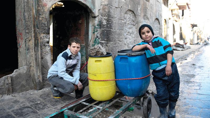 أطفال يحملون الماء على عربة إلى منزلهم في شرق حلب.  رويترز