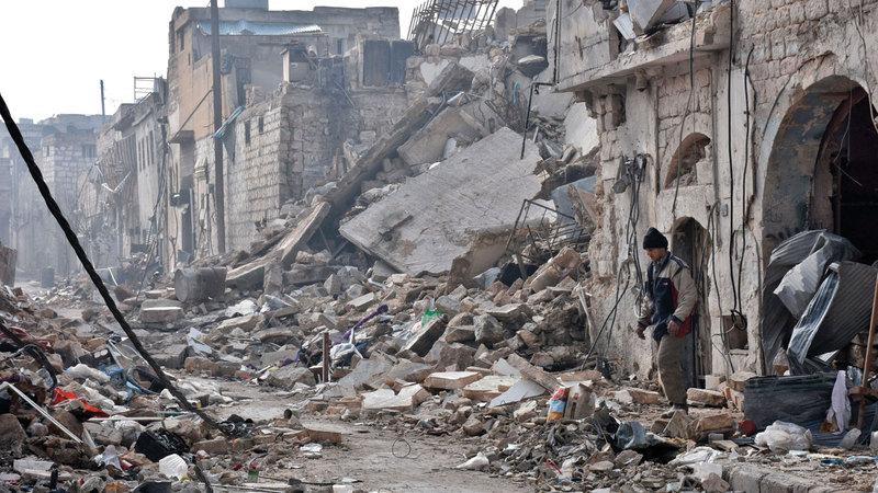 رجل يمشي وسط ركام المنازل المدمّرة في حلب. أ.ف.ب