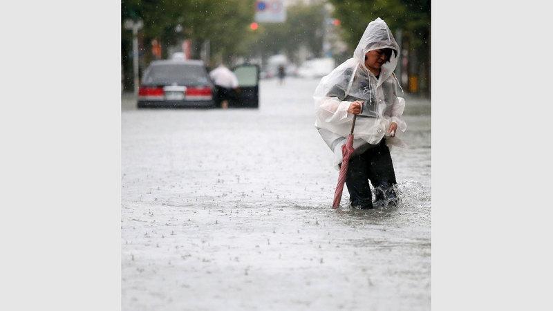 تضع غطاء رأس لوقاية نفسها من مياه المطر.  أ.ف.ب