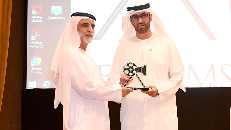 الجابر يسلّم غلوم جائزة العطاء الفني. تصوير: إريك أرازاس