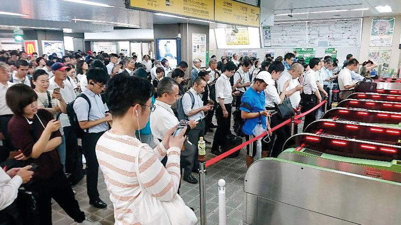 ركاب ينتظرون عودة خدمة القطارات بعد انقطاعها في طوكيو.  أ.ب