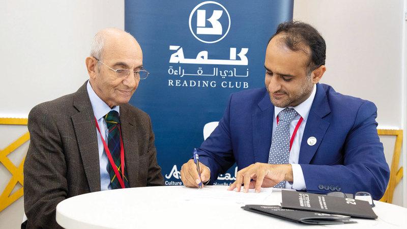 آل علي (يمين) يوقّع على إحدى اتفاقيات الترجمة.  من المصدر